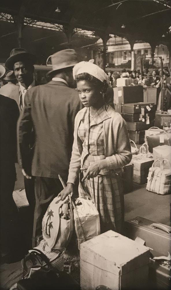 This photo from the British Library exhibition depicts a newly arrived West Indian woman, waiting with her luggage. Photo courtesy The British Library