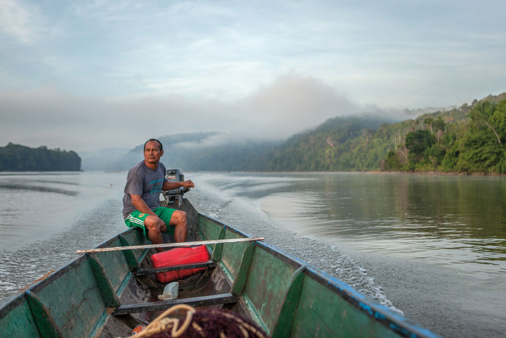 Dosu Pelenapin pilots his boat on the Lawa, one of the rivers that forms the boundary between Suriname and French Guiana. Photography by Milton Kam