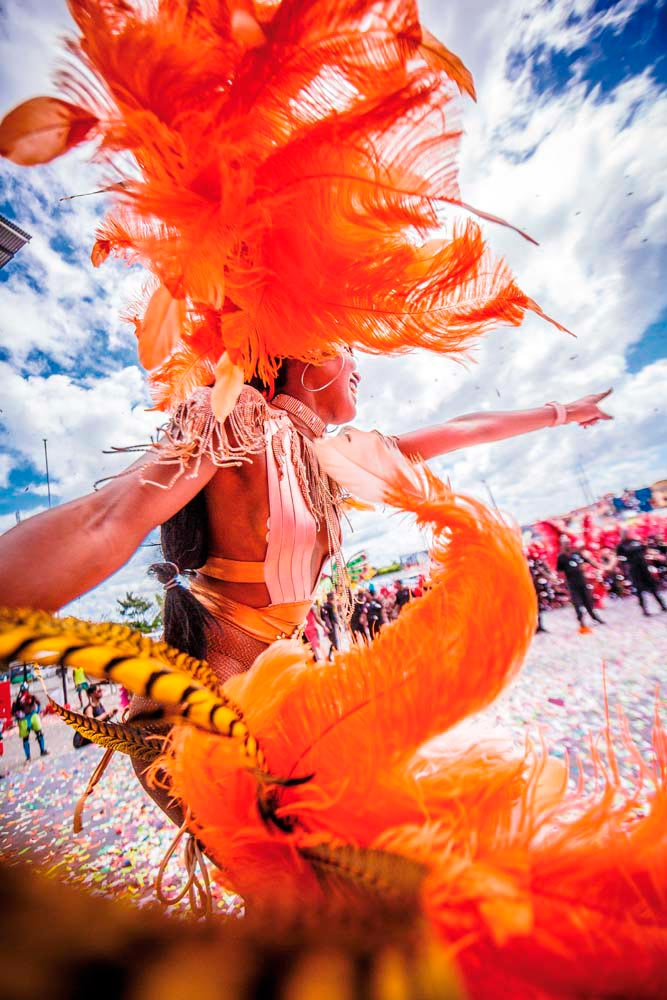 A masquerader from the band Yuma crosses the stage in a whirl of floating feathers. Photo by Dwayne Watkins Photography