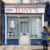 The façade of Ruby Cruel, Blue Curry's new arts space in a former barbershop in east London. A handpainted sign by Trinidadian Bruce Cayonne is displayed in the front window. Photo courtesy Blue Curry