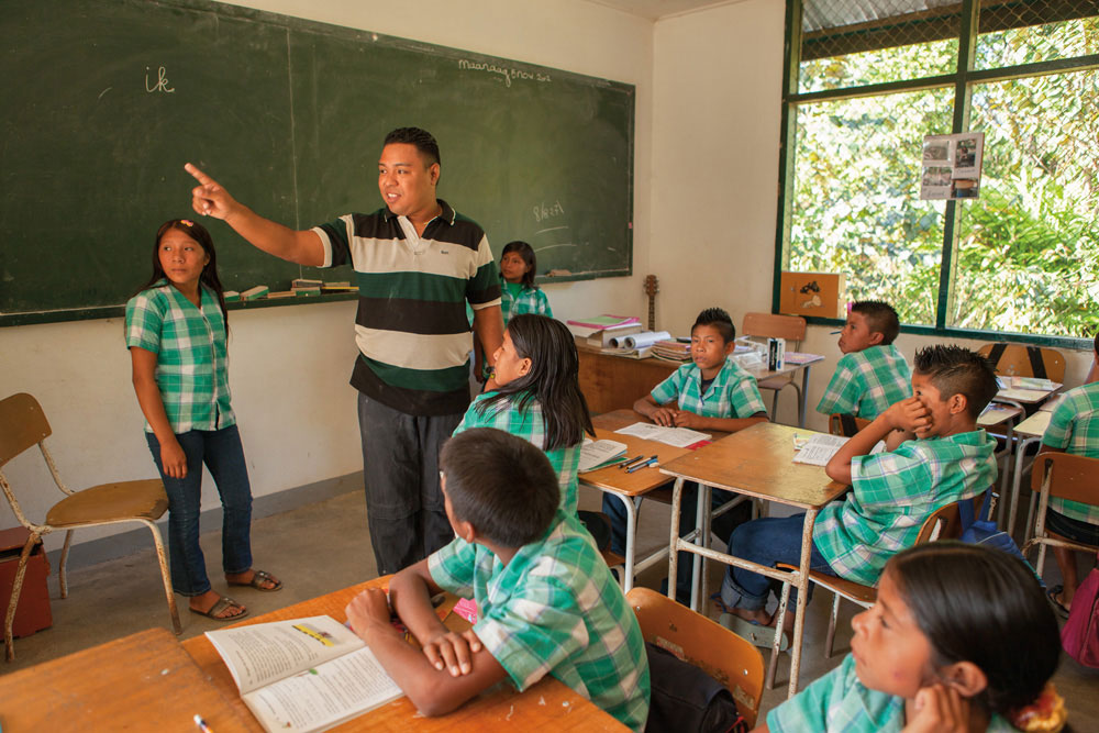 """Students pay attention as Arnold Arupa instructs them in Dutch, the official language of the education system in Suriname. As the principal of the Kananoe primary school in Apetina, he is aware of the educational hurdles indigenous children face. """"I want to be a role model and an example of what they too can become. I want them to continue to appreciate and develop their culture and language."""" In his work, Arupa uses examples from their Wayana culture. If a textbook uses a bus to make a point, he will instead use a canoe as an example. """"I look for points of recognition, and that helps a lot"""". Photography by Milton Kam"""