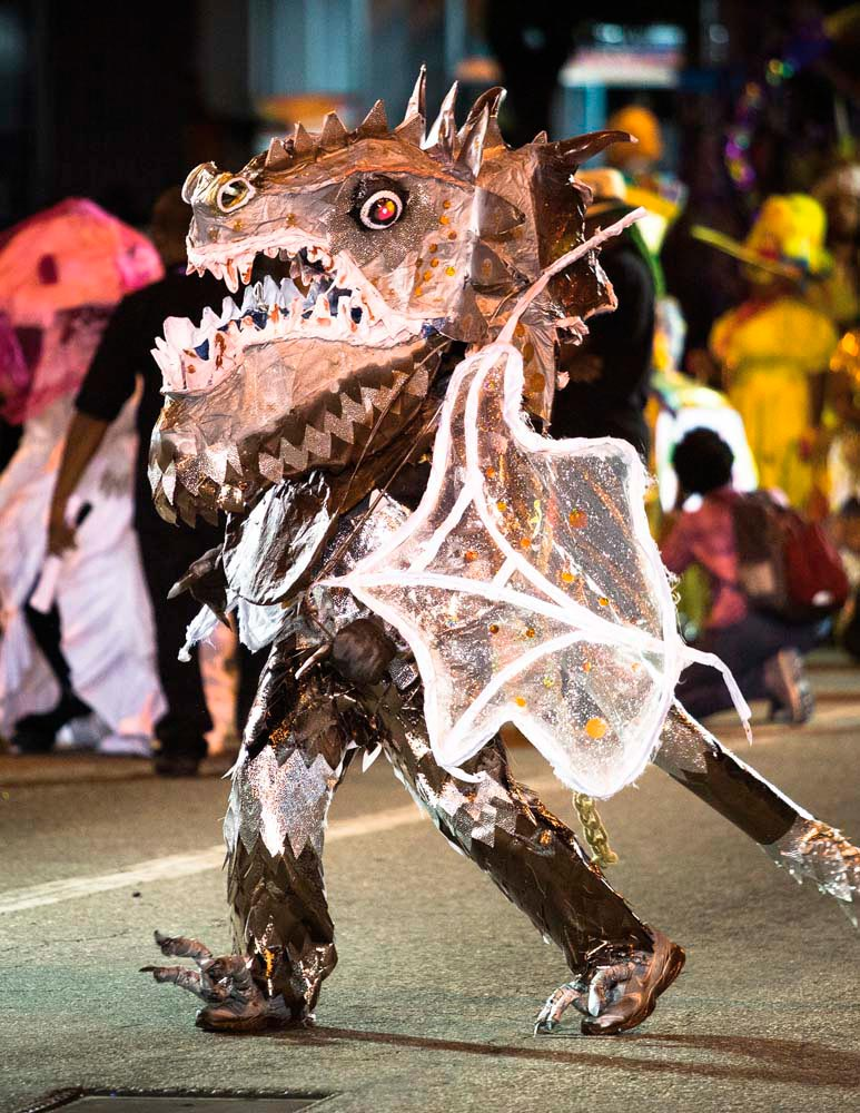 With its scales and horns, wings and fearsome eyes, gaping jaws and jagged fangs, the dragon — portrayed here by Junior Taylor — represents barely restrained brutality in a traditional devil band. Photo by Maria Nunes