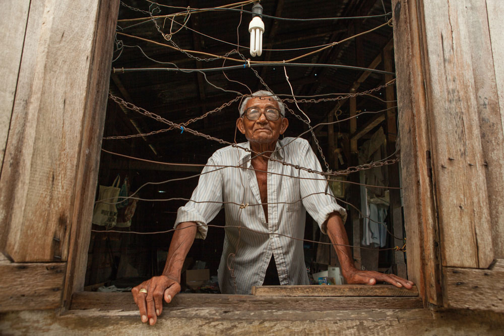 """""""He gave me advice when I had problems with the government and he also encouraged me to keep fighting for our land rights,"""" says Pikin Poika village chief Joan van der Bosch about her great-uncle Nicodemus Hoogland. He is seen here in the window of his village shop, which he operated after his retirement from the meteorological service. Photography by Milton Kam"""