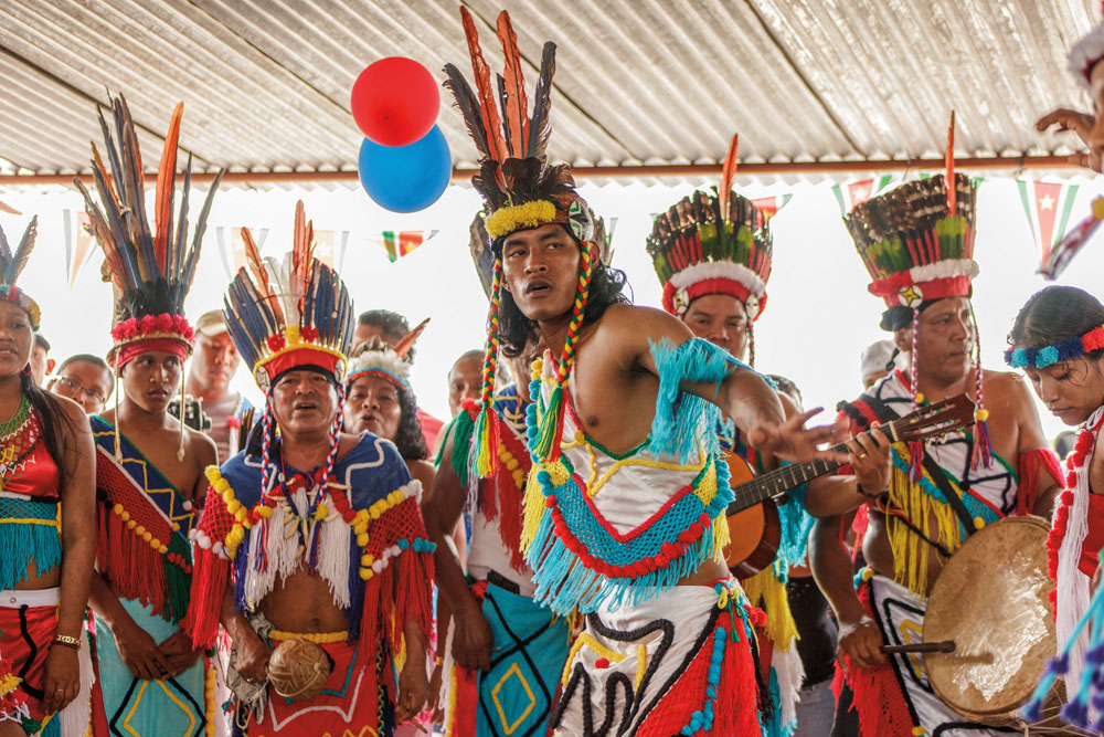 "David Benschop performs a war dance with the cultural group Waiono during the inaugural ceremony of Ronald Makosi in Powakka. ""The war song and dance serve as a reminder to the newly elected village leader of how the Lokono people have fought wars again"