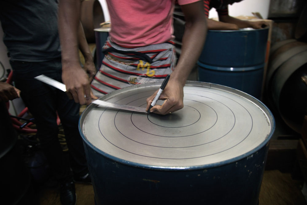 Kaijah Codrington marks the surface of the steel drum prior to sinking it. Photography by Mark Lyndersay