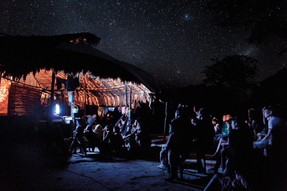 Under an endless expanse of stars, villagers gather for a night of entertainment in Sipaliwini Savanne. Photography by Milton Kam