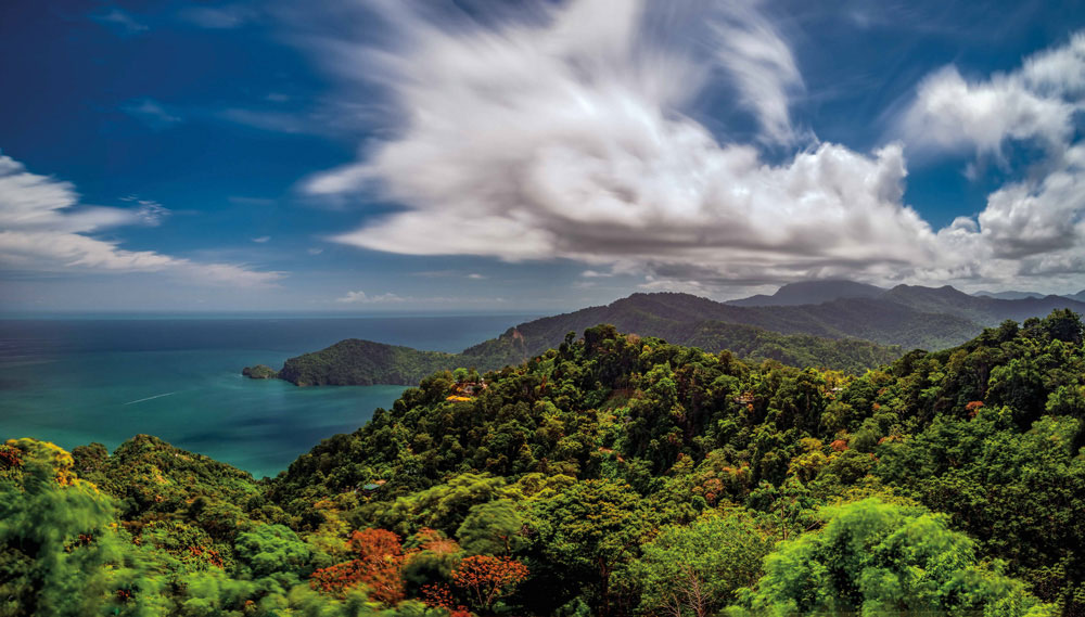 """A view along Trinidad's north coast, looking east from Paramin across vertiginous forested slopes dotted with flaming immortelle trees. Photographer Jason Audain remembers the moment: """"It was taken at sunrise while we were passing through the [Paramin] track. The angle was epic, and I needed to capture it to make the moment last."""" Photo by Jason Audain"""