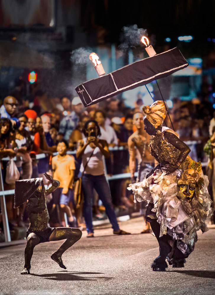 Maswoman Tracy Sankar-Charleau has won a devoted following for her intense portrayals of original characters inspired by Carnival's macabre traditions — like this Lady of the Night bearing a flaming coffin and accompanied by a prancing douen, Sankar's son Jude. Photo by Maria Nunes