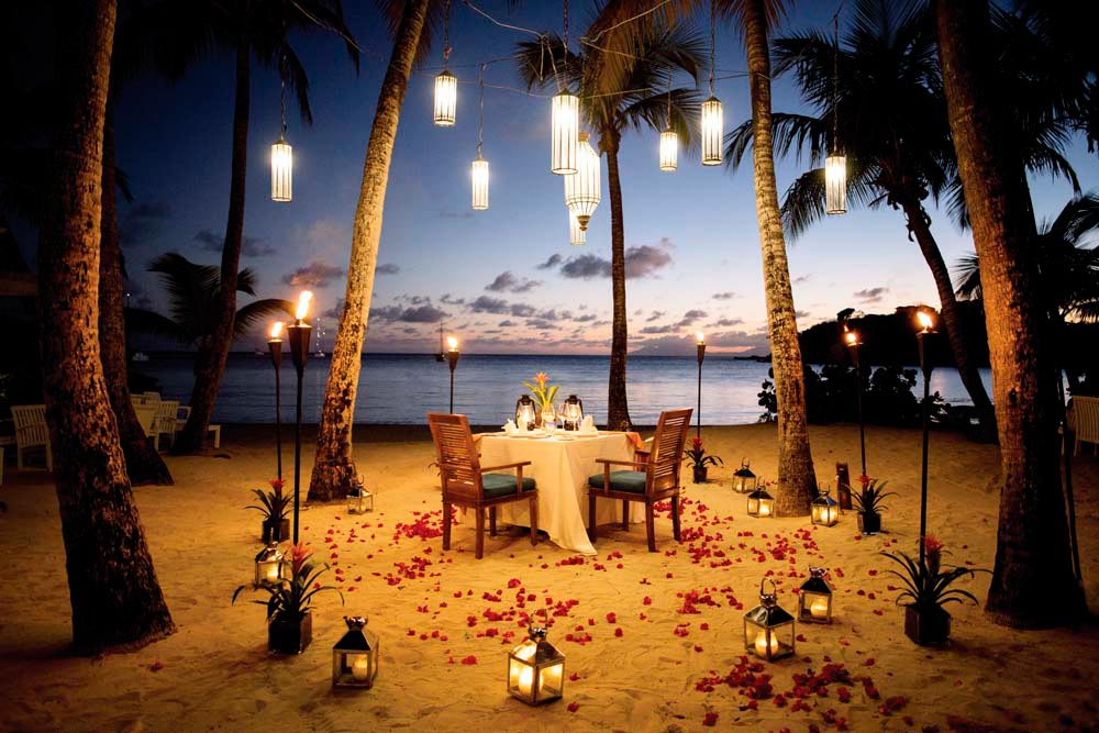 A candlelit dinner for two, on the beach in Antigua — no better way to start the honeymoon. Photo by JoshoJosho/Shutterstock.com