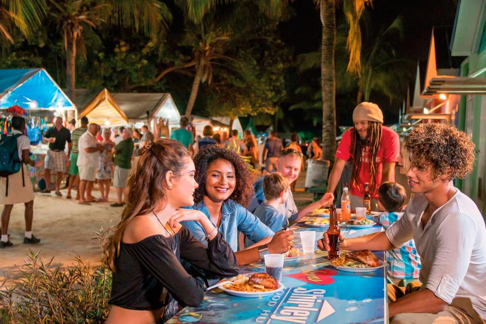 Enjoying the vibe — and the food — at the Friday-night fish fry in Oistins. Photo courtesy Barbados Touyrism Marketing Inc