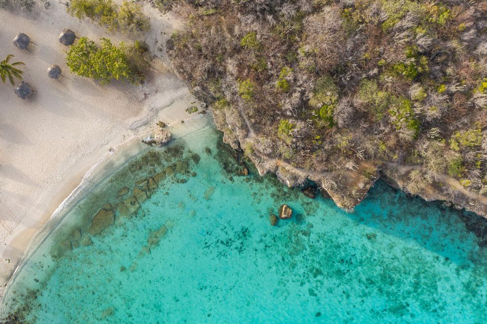 At Daaibooi Bay near the village of Sint Willibrordus, limestone cliffs shelter a pristine turquiose bay. Photo by Naturepixfilms/Shutterstock.com