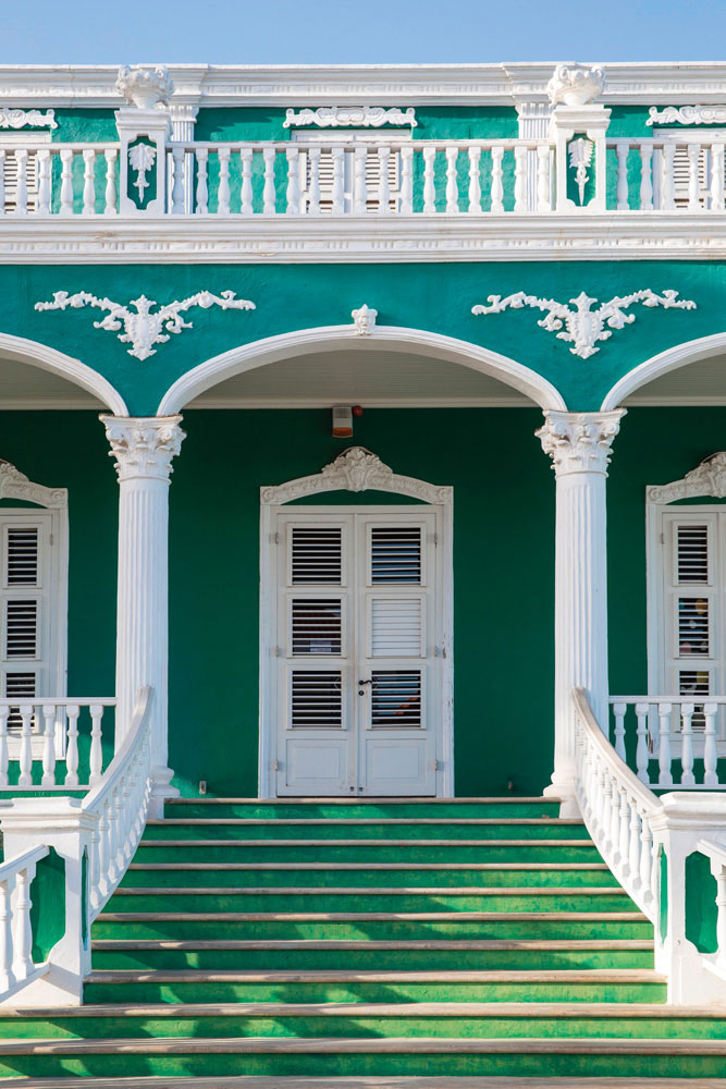The ornate façade of a historic building in Willemstad's Pietermaai district. Photo by Robertharding/Alamy Stock Photo