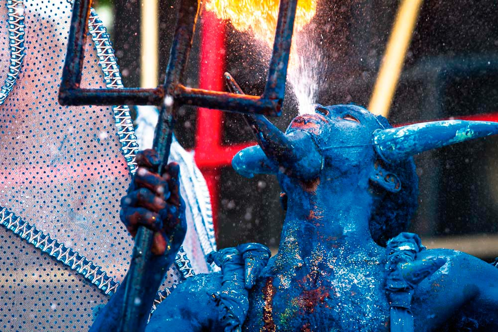 Blue devils, Trinidad Of the various species of devil mas among Trinidad's traditional Carnival masquerades, blue devils are by far the most celebrated — a favourite of photographers, subject of films and books, and perennial crowd-pleasers. On Carnival Monday, the place to see them is their home ground: as far back as anyone can remember, the village of Paramin in the hills north of Port of Spain has been home to rival blue devil troupes, with their blood-curdling hoots and menacing dance to the rhythm of drums, breathing fire and mock-menacing onlookers with their pitchforks. Photo by Maria Nunes