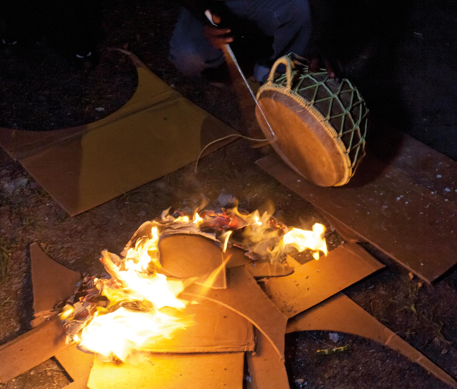 Heating a goatskin kettledrum to tune its pitch. Photograph by Mark Lyndersay