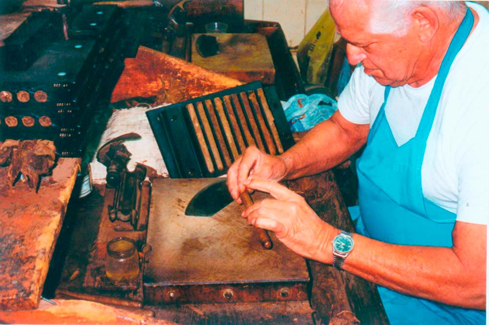 A worker puts the final touches to a cigar at El Credito cigar factory. Photograph by Simon Lee