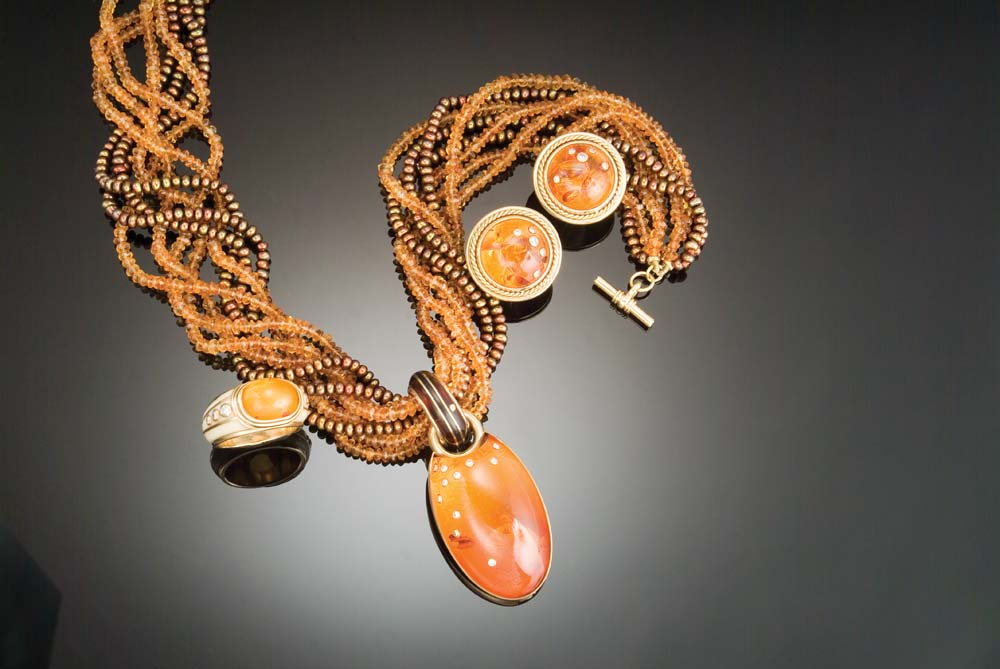 Gold, ivory, amber, and diamond ring; pair of gold, amber, and diamond earrings; necklace of citrine beads and gold-coloured seed pearls with a turtle-shell, ebony, gold, amber, and diamond pendant. Photo by Michele Jorsling
