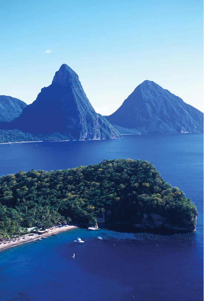 St Lucia's Pitons — Petit to the left, Grand to the right — with Grande Caille Point in the foreground. Photo courtesy The St Lucia Tourist Board