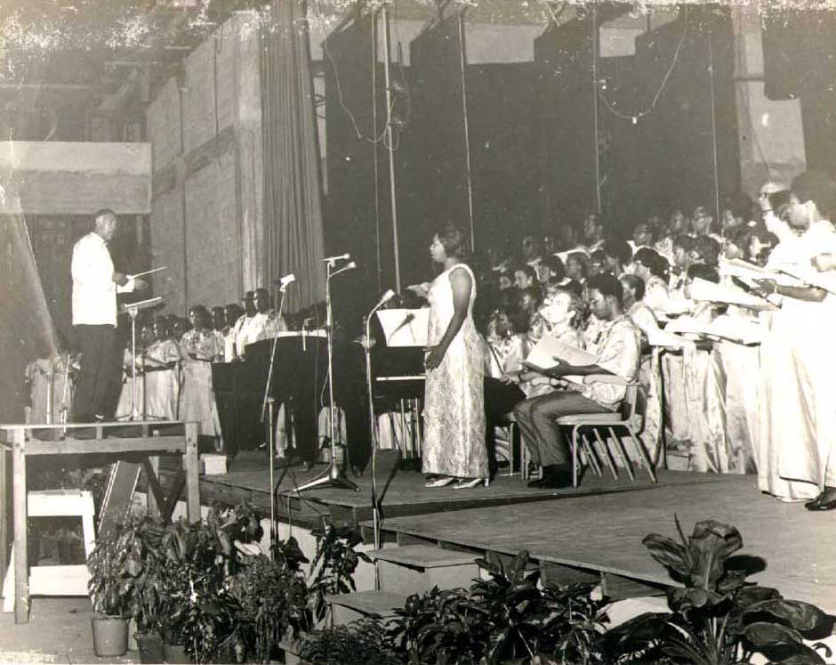 Bill Pilgrim, brother of composer Philip Pilgrim, conducts a performance of The Legend of Kaieteur at the National Cultural Centre in Georgetown, Guyana, during the 1972 Caribbean Festival of Culture and Arts, Soloist Barbara Burrows stands at centre-stage. Photograph courtesy Bill Pilgrim
