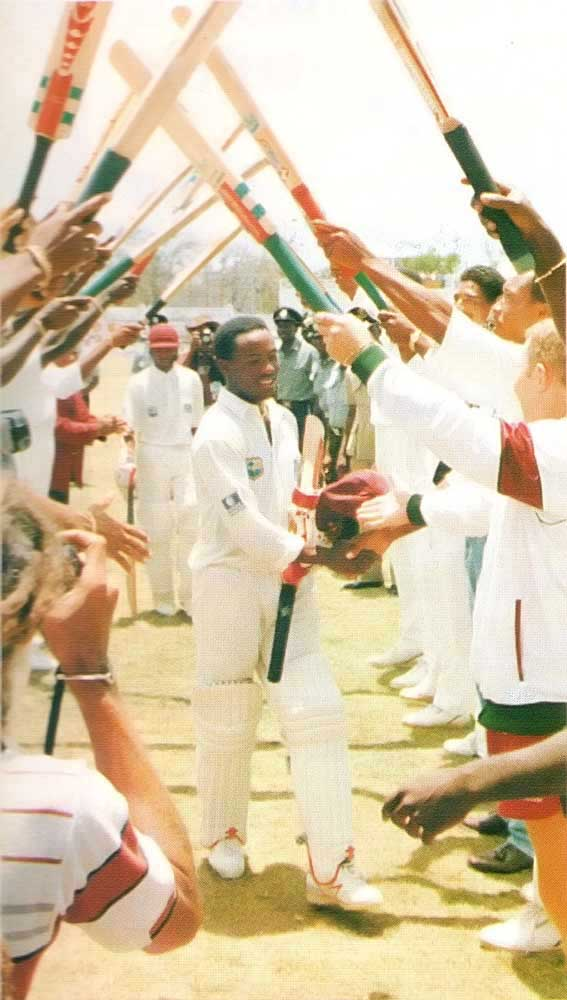 Laramania: players form a triumphal arch after Brian Lara's record breaking Antigua innings. Photograph by Allan Aflak
