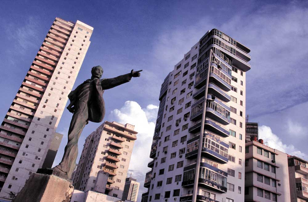 High-rise apartment buildings on the Malecon, with a statue of Jose Marti in the foreground. Photograph by Sean Drakes