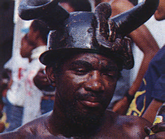 A jab-jab dancer (with devil's helmet and friend) enjoys the Local beer. Photograph by Merle Gunby