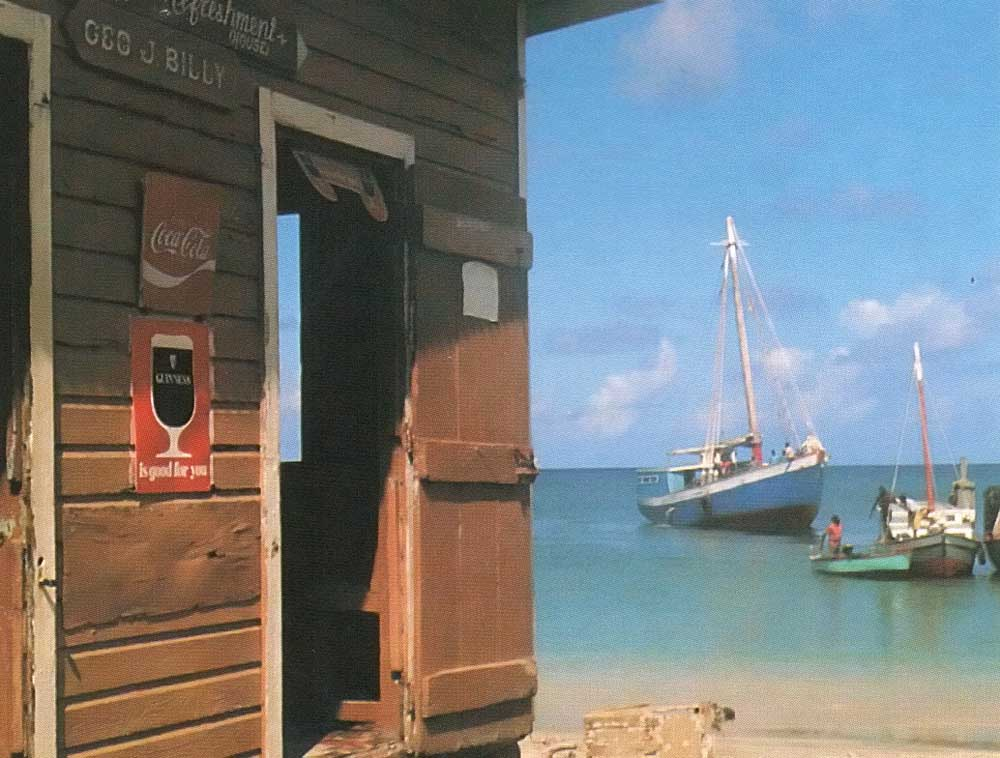 "The Golden Eagle bar in Hillsborough Carriacou; the mail boat and an ""engine"" boat from Union Island in the background. Photograph by Frances Kay"