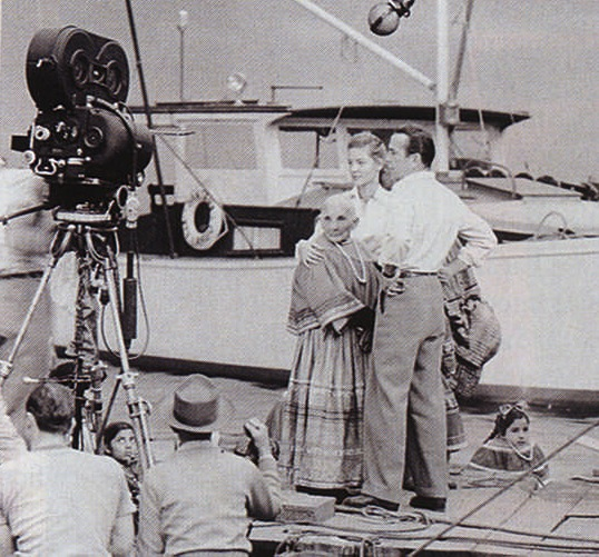 Humprey Bogart and Lauren Bacall talk through a scene with Seminole Indian extras in Key Largo (1948). Photograph by the British Film Institute
