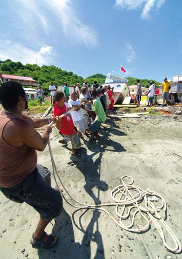 Community members help launch a newly built boat. Photograph by Orlando Romain