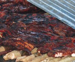 Jerk pork smokes to perfection over pimento wood, covered by zinc fencing panels. Photograph by Rosemary Parkinson