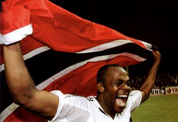 Stern John goes wild with a Trinidad and Tobago flag moments after the team`s 1-0 win over Bahrain. Photograph courtesy Medianet Ltd