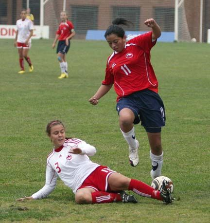 Chilean forward Yudith Rojas (red and blue) captures the ball in a friendly match against Canada on July 29. Photograph courtesy the Chilean Football Federation