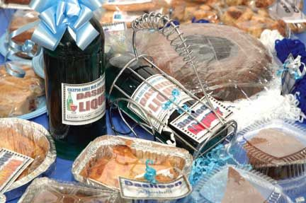 The table that won `best display` at the Blue Food festival, showing pastries, cakes, cookies and a liqueur. Photograph by Oswin Browne