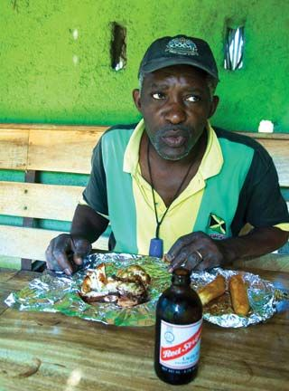 A Scotchies regular tucks into the classic combination of jerk chicken washed down with a cold Red Stripe. Photograph by Paul Marshall