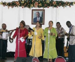 Claire Piper (in red) serenades guests at President`s House, Trinidad. Photograph courtesy E Matthews