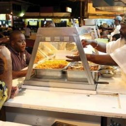 Ossie Francis, better known as Chinkey, serves some of his customers in St James, Trinidad. Photograph by Andrea De Silva