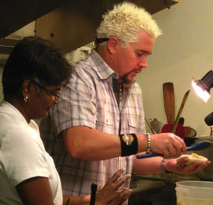 Guy Fieri (right) with Pamela Jacob from Pam`s Kitchen on Fieri`s television show Diners, Drive-ins and Dives. Photograph courtesy Anjuli Jacob