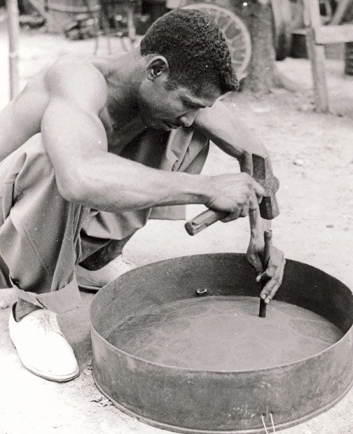 Ellie Mannette tuning a pan in Invaders panyard, Tragarete Road, mid-1950s. Photograph by Jean Pearse