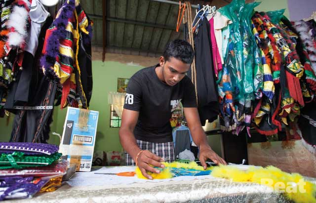 Ronaldo Alfred works on his Jab Jab costume at his family workshop in Carapichaima, Trinidad. Photograph by Mark Lyndersay