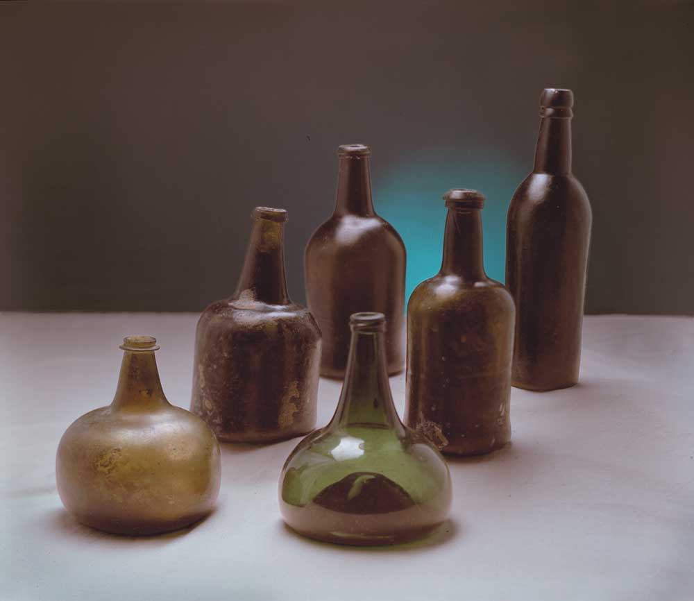"""From the early 1600s to the 19th century, wine, spirits and utility bottles evolved continually and subtly. Front row from left: English """"pancake""""-style """"onion"""", 1680–1700; Dutch """"onion"""", 1700–1740. Second row: transitional """"mallet"""", 1740–1760; early squat cylinder, 1750–1760. Third row: a more developed squat cylinder, 1780–1800; cylinder bottle, post-1800. Photograph by Eric Young"""