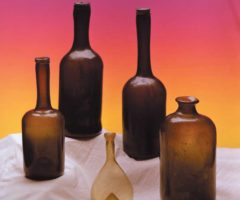 """Black glass wine and utility bottles dominated the 1700s, though some houses devised recipes for new colours. These specimens come from Guyana. Front row from left: Dutch mini """"lady's leg"""", also called a """"long neck""""; small Belgian thin-walled flask, c1700; Dutch utility bottle, also called a """"snuff"""", late 1700s. Back row: two standard Dutch """"lady's legs"""". Photograph by Eric Young"""