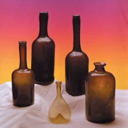 "Black glass wine and utility bottles dominated the 1700s, though some houses devised recipes for new colours. These specimens come from Guyana. Front row from left: Dutch mini ""lady's leg"", also called a ""long neck""; small Belgian thin-walled flask, c1700; Dutch utility bottle, also called a ""snuff"", late 1700s. Back row: two standard Dutch ""lady's legs"". Photograph by Eric Young"