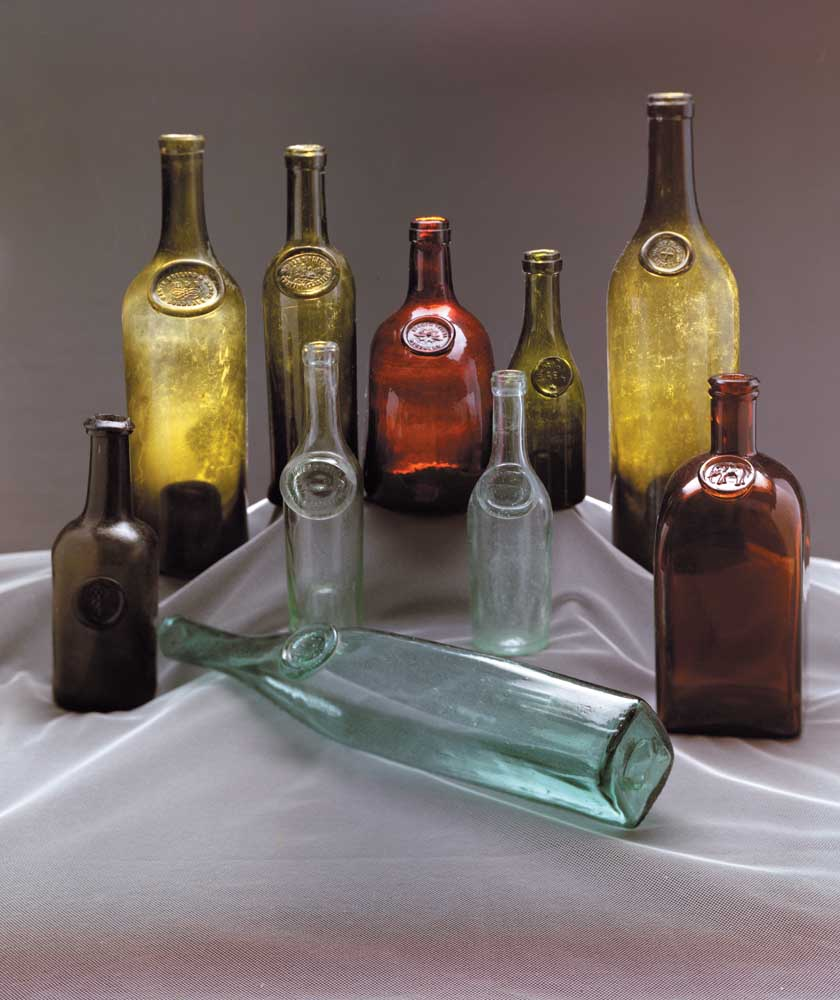 """Bottle collectors often date their finds by comparing the applied seals on bottles of similar shape. Lying down at front: early 1800s pontilled """"zara"""" wine bottle, from a region now part of Italy. Front row from left: one of the earliest known seal bottles found in Barbados waters, 1700s; two small aqua olive oil bottles; German liquor bottle with an elephant seal, late 1800s. Back row: wine bottle with """"Marie Brizzard & Roger"""" seal, 1870s; bell-bottomed olive oil bottle, c1850; flat-sided German wine bottle; """"captain's"""" wine bottle with """"Bourneramp AE"""" seal; French Pernod Fils wine bottle, mid-1800s. Photograph by Eric Young"""