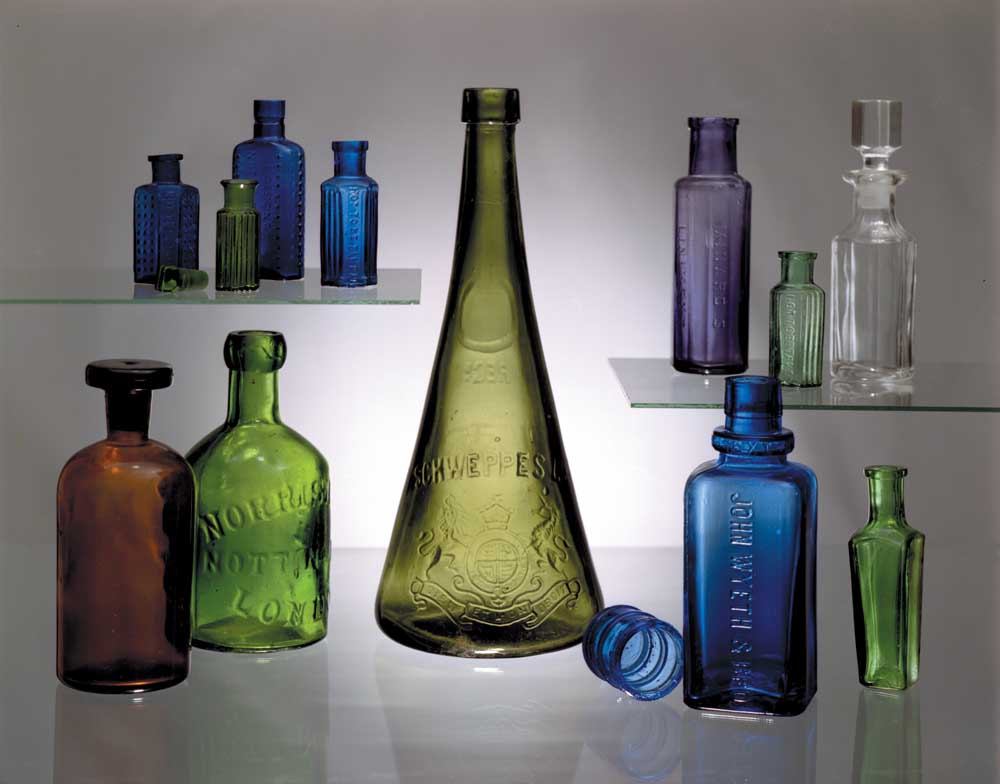 """By the late Victorian era many bottles were machine-produced, with the neck and lip still applied by hand. Bottle-makers sought to produce eye-grabbing colours, shapes and heavy embossing. Top left: three cobalt blue poison bottles and a tiny green pharmacy bottle. Top right: amethyst liniment bottle; green poison bottle; glass-stoppered cut crystal bottle, probably for cologne or toilet water. Bottom left: brown pharmacy bottle with glass stopper; """"blob"""" mineral water bottle, embossed """"Norrish & Co., London"""". Bottom right: Cobalt blue medicine bottle with its own dose cap; small green concave-sided condiment bottle. Centre: a rare turn-of-the-century 12-inch embossed Schweppes soda bottle. This short-lived shape did not find favour with patrons, due to its tendency to slip from sweaty hands! Photograph by Eric Young"""