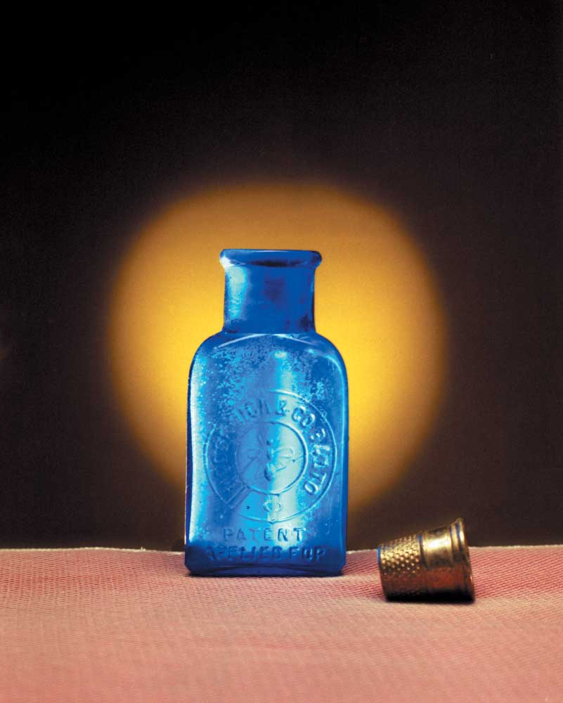 """Three-inch-tall triangle cobalt medicine bottle, embossed """"McCormick and Co."""", with a bee in the centre of the insignia. Photograph by Eric Young"""
