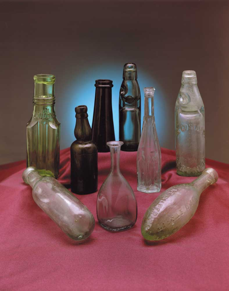 """Aerated mineral water and other drinks were all the rage in the early 1800s, due to the purported healing properties of spa waters from Germany, England and other countries. Soon a process was invented  for artificial aeration and businessmen like Joseph Schweppe seized the opportunity to mass-produce seltzer and soda water. Front row from left: round-bottomed """"hamilton"""" aerated water bottle; pontilled flare-lip utility bottle; early torpedo-style """"hamilton"""". Second row: pickle or caper bottle, interesting for its decorative ribbing and embossing; three-piece-mold bent-neck pygmy beer bottle, mid-1800s; cathedral-style sauce bottle, named for its """"cathedral window"""" panes; embossed """"Da Costa & Co., Barbados"""" codd bottle. Back row: French black glass truffle bottle, 1860s; unusual small teal-coloured root beer codd with a matching teal marble in the pinch. Photograph by Eric Young"""