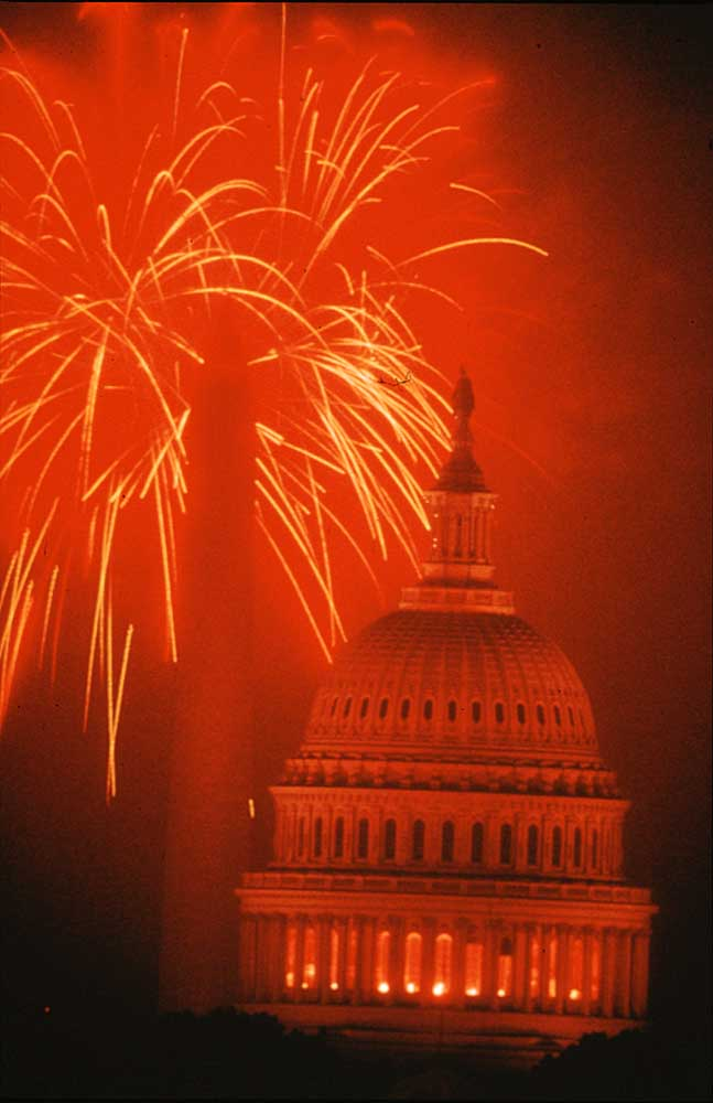Fourth of July Fireworks over the Capitol dome. Photograph by Washington Dc Convention & Visitors Association