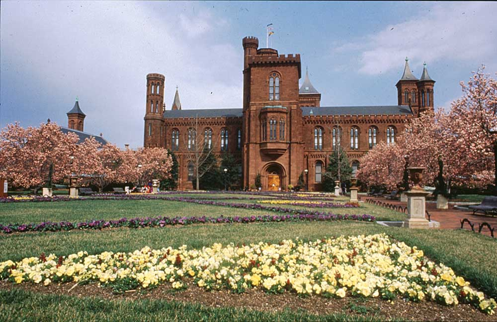 """Smithsonian """"Castle"""" Building, with spring blossoms. Photograph by J Mcguire/Washington DC Convention & Tourism Corporation"""