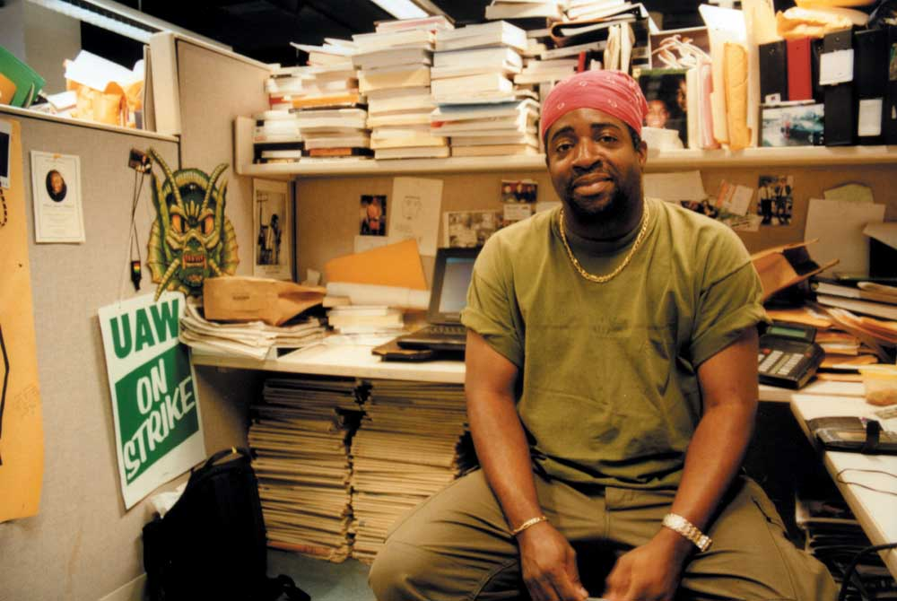 """Peter Noel """"profiling"""" in his Village Voice cubicle, June 2000. Photograph by Georgia Popplewell"""