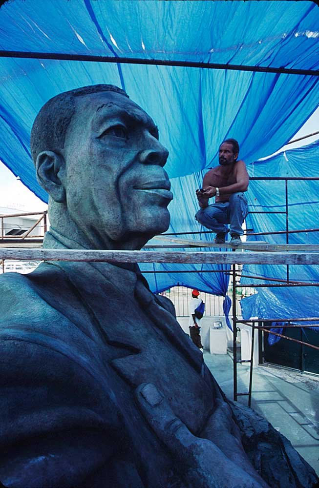 Cuban artist Andres Gonzales admires his rendition of former Prime Minister, VC Bird. Photograph by Sean Drakes/ Blue Mango