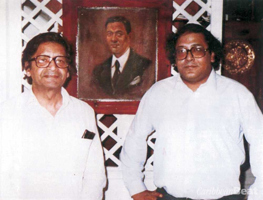 Naipaul was devastated when his younger brother Shiva (right), also a successful writer, died in 1985 at the age of 40. They are standing in front of a portrait of their father Seepersad. Photograph courtesy Kamla Naipaul-Tewari
